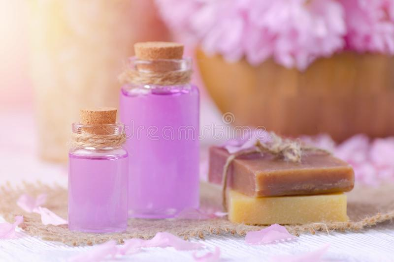Beautiful spa composition with massage oil, soap bar and fresh pink flowers. Selective focus, toned royalty free stock image