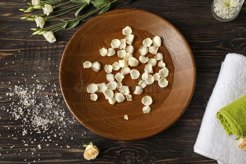 Beautiful spa composition with plate of water and flower petals in salon royalty free stock photos