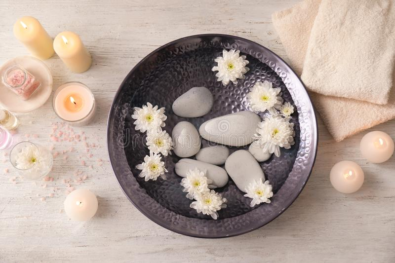 Beautiful spa composition with plate of water, flowers and candles in salon stock photo