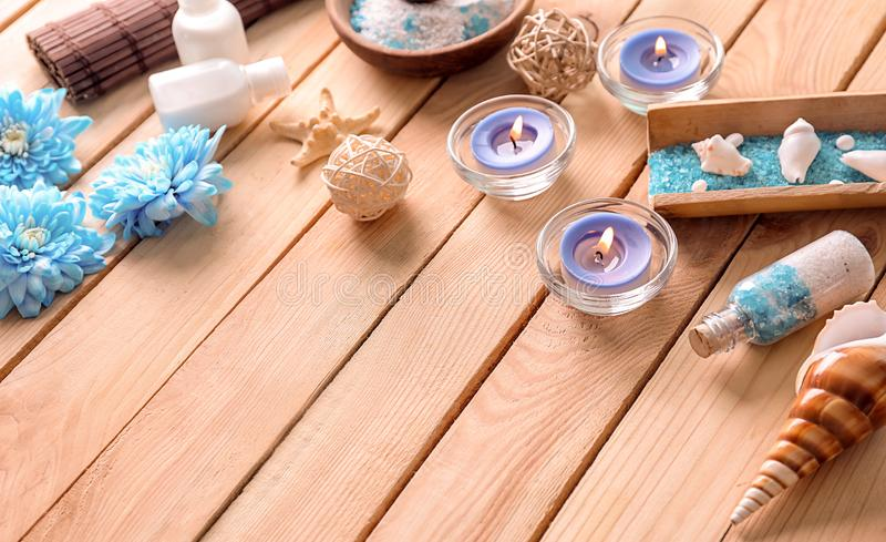 Beautiful spa composition with sea salt, shells and candles on wooden table stock photography