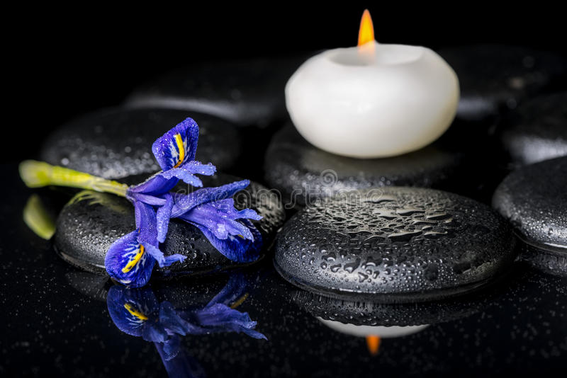 Beautiful spa concept of blooming iris flower, candles and black zen stones. On reflection water, closeup royalty free stock photography