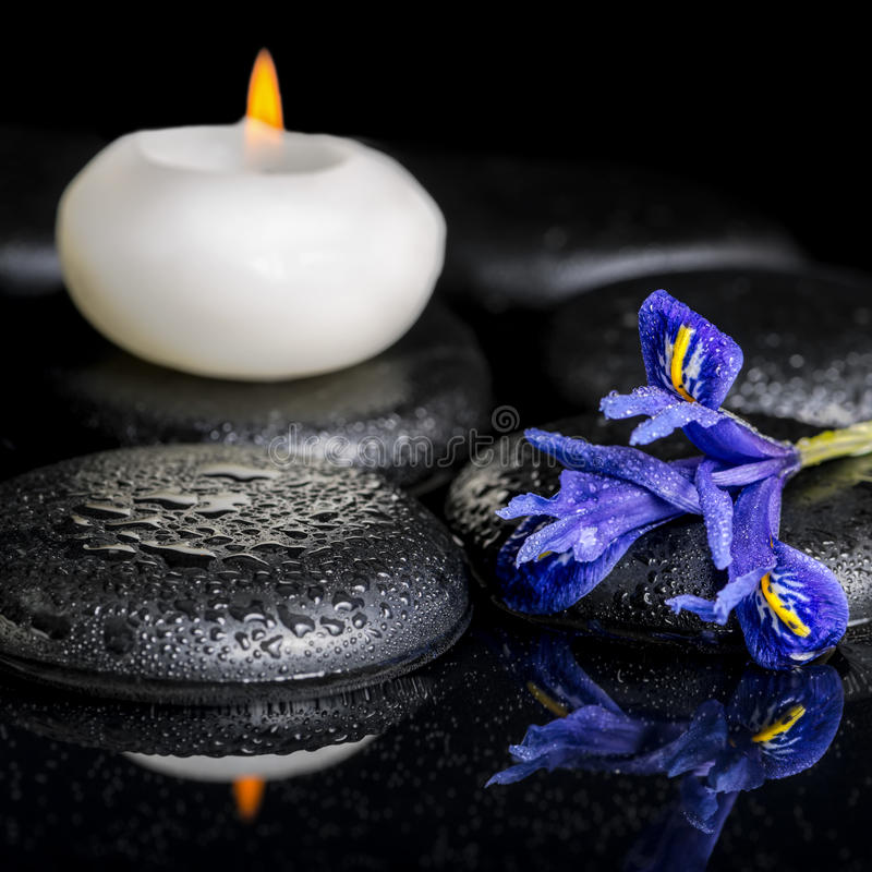 Beautiful spa concept of blooming iris flower, candles and black. Zen stones on reflection water, macro stock photo
