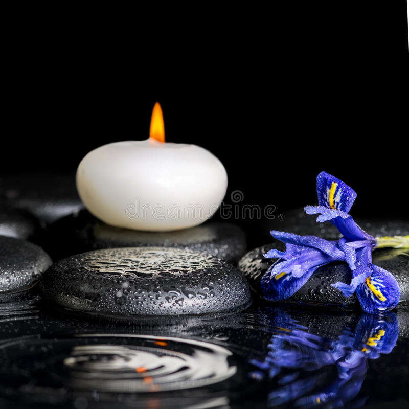 Beautiful spa concept of blooming iris flower. Candles and black zen stones on ripple reflection water, closeup stock image