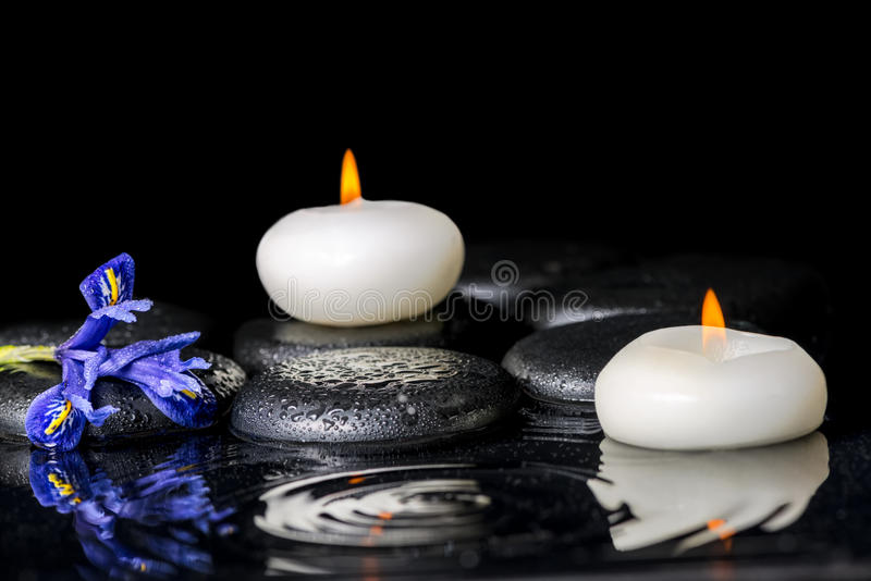 Beautiful spa concept of blooming iris flower, candles and black. Zen stones on ripple reflection water, closeup royalty free stock photography