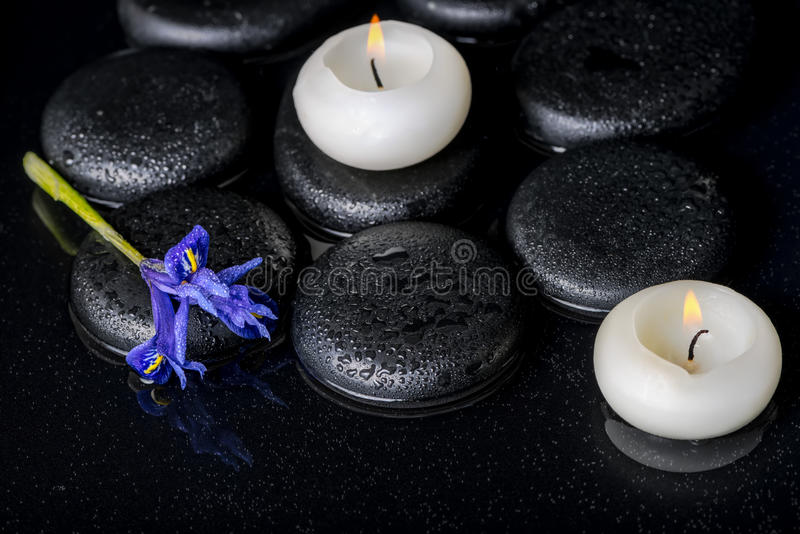 Beautiful spa concept of blooming iris flower, candles and black. Zen stones on water, closeup royalty free stock image