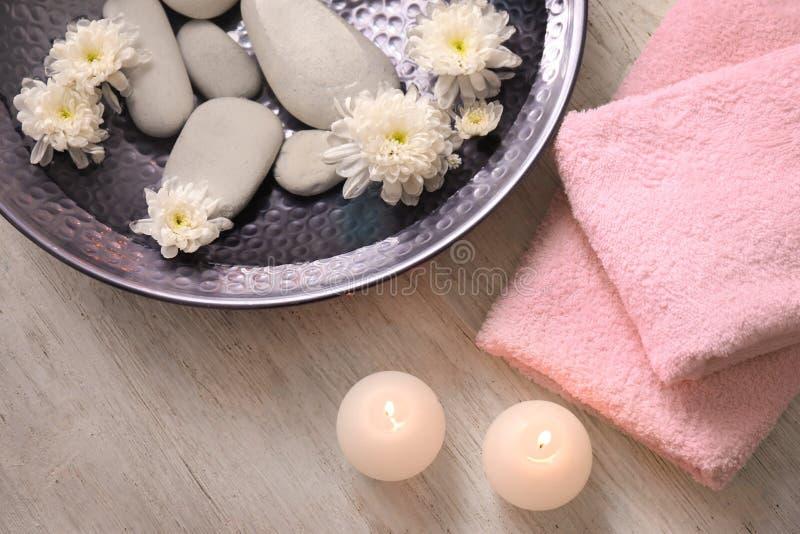 Beautiful spa samenstelling met plaat van water, bloemen en kaarsen in salon stock foto