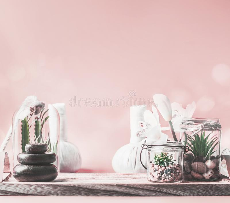 Beautiful spa setting background with steak of massage stones, succulent plants and wellness equipment on table at pastel pink royalty free stock photo