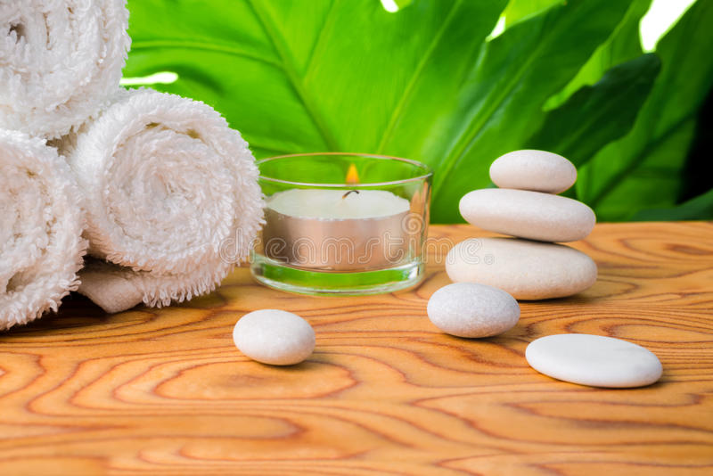 Beautiful spa setting of stones, candle, rolled white towels and green leaf on root wood background. Close up royalty free stock images