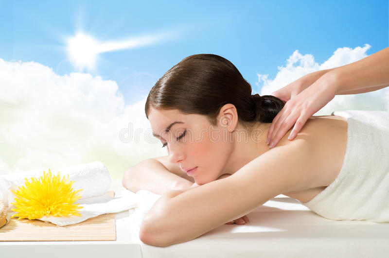 Beautiful spa woman lying on the couch. In front of her flower and rolled towel stock photo