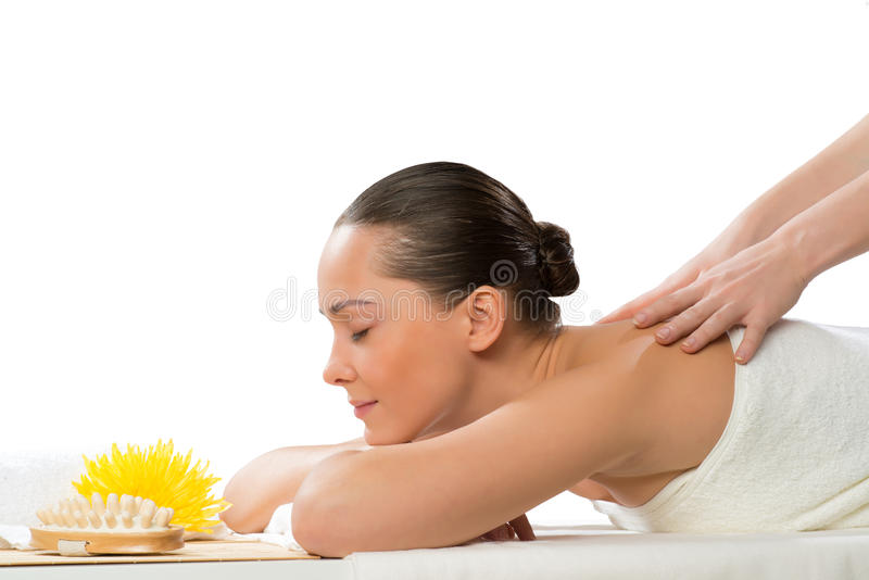Beautiful spa woman lying on the couch. In front of her flower and rolled towel royalty free stock photo