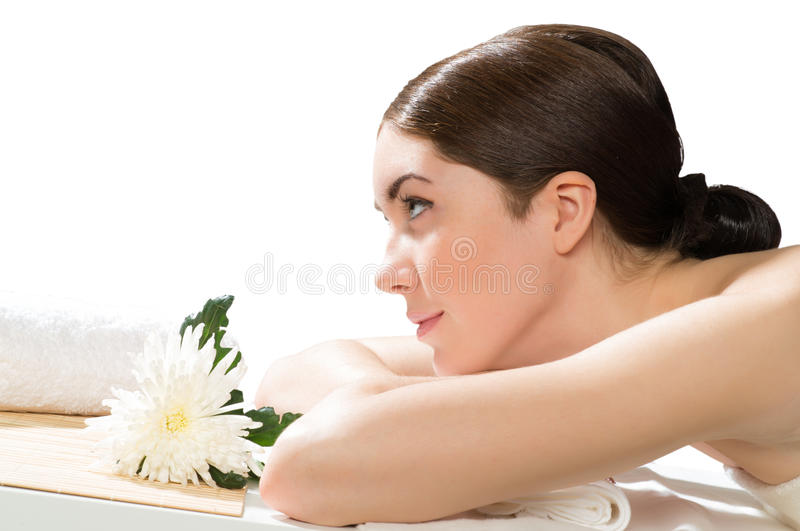Beautiful spa woman lying on the couch. In front of her flower and rolled towel royalty free stock photos