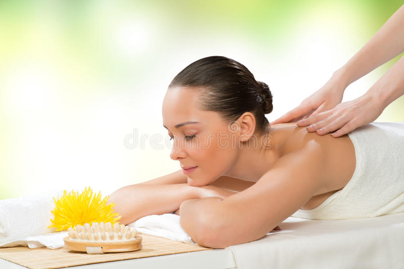 Beautiful spa woman lying on the couch. In front of her flower and rolled towel royalty free stock photography