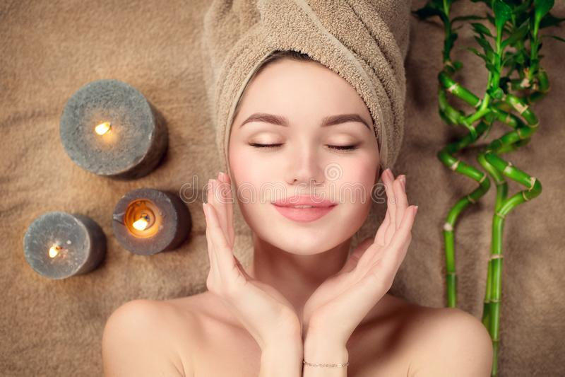 Beautiful spa woman with a towel on her head lying and touching face skin. Skincare stock photo