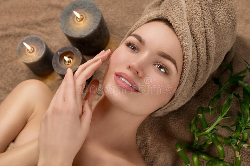 Beautiful spa woman with a towel on her head lying and touching face skin. Skincare. Beauty smiling model girl in spa salon. Skin care, acne treatment stock image