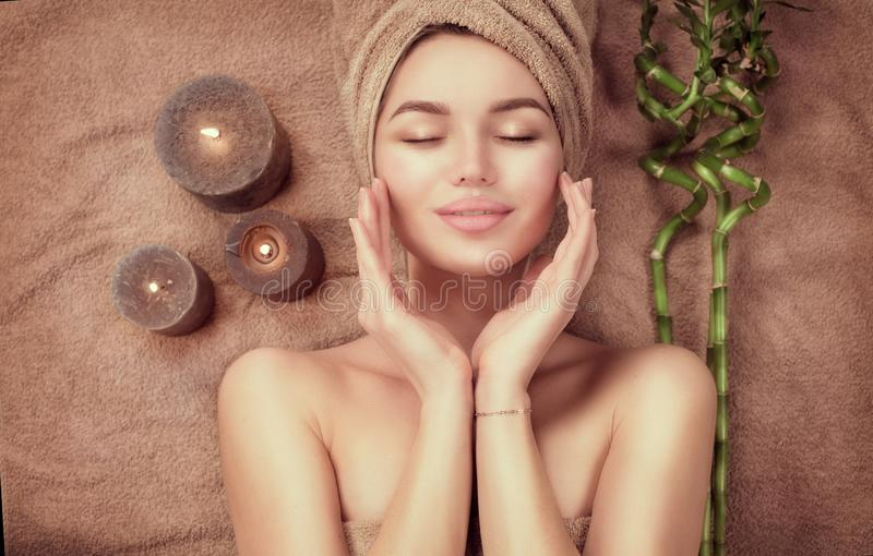 Beautiful spa woman with a towel on her head lying and touching face skin. Beauty smiling model girl in spa salon royalty free stock photos