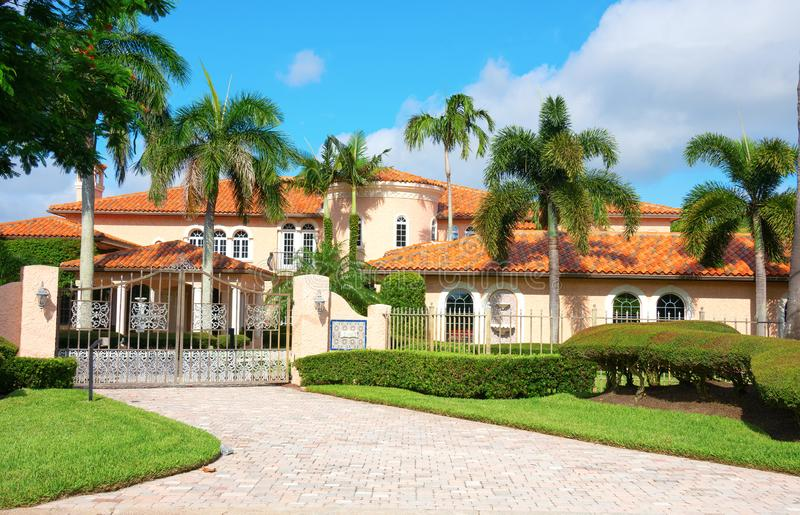 Beautiful Spanish style luxury mansion residential home with a privacy gate and palm trees stock photo