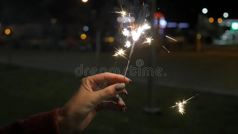 Beautiful sparkler in woman hand on black or street background. Woman holding sparkler against colorful defocused lights royalty free stock photos