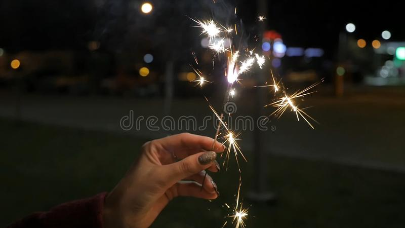 Beautiful sparkler in woman hand on black or street background. Woman holding sparkler against colorful defocused lights royalty free stock image