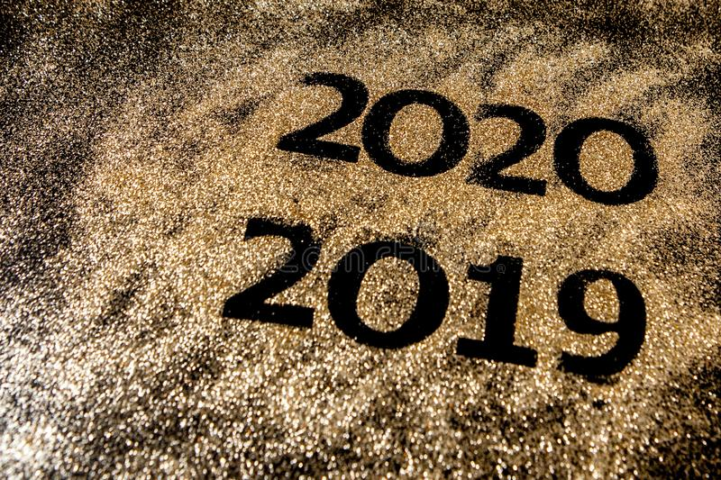 Beautiful sparkling Golden Numbers of 2019 to 2020 on black background for design, happy new year concept stock photography