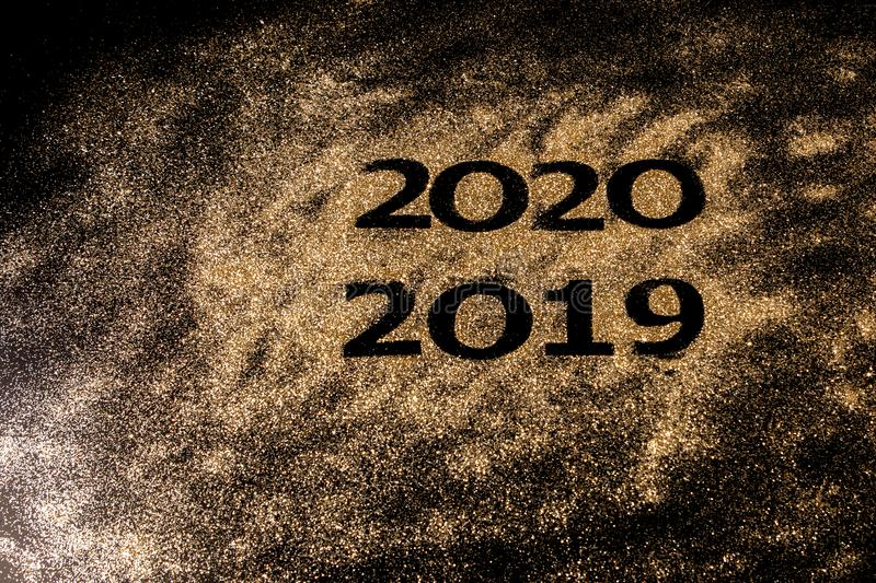 Beautiful sparkling Golden Numbers of 2019 to 2020 on black background for design, happy new year concept royalty free stock image