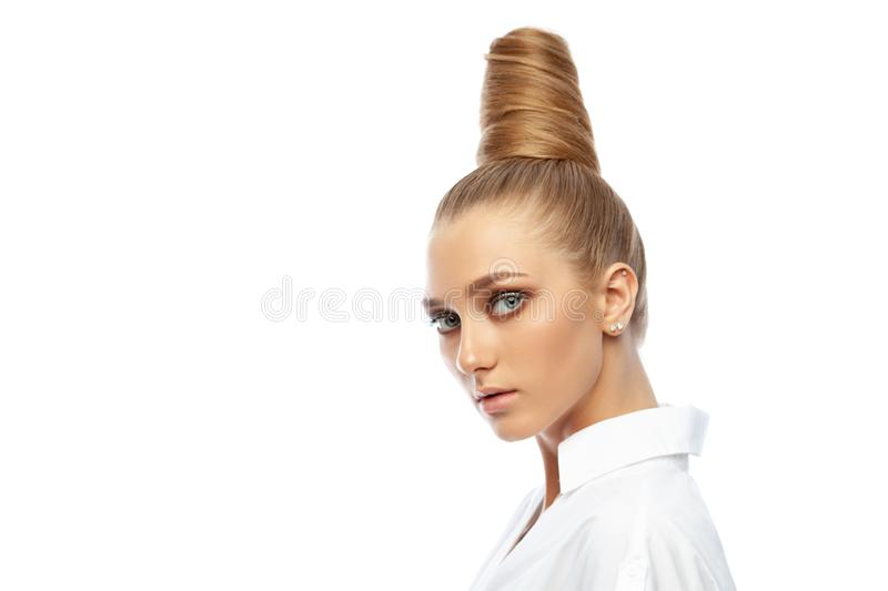 Beautiful spectacular blonde lady with an unusual high hairdo with big blue eyes on a white background royalty free stock images