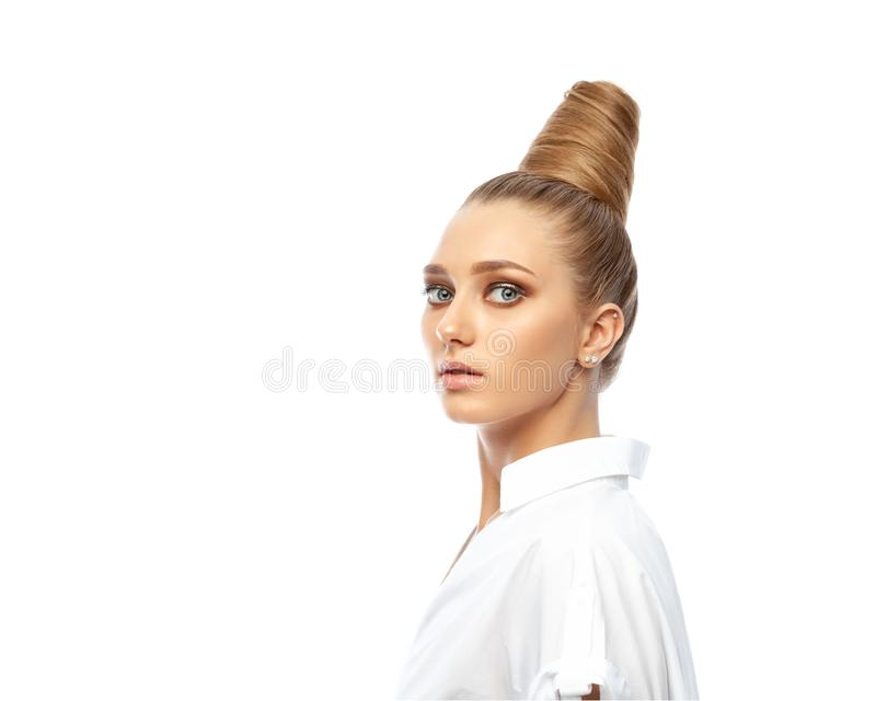 Beautiful spectacular blonde lady with an unusual high hairdo with big blue eyes on a white background royalty free stock image