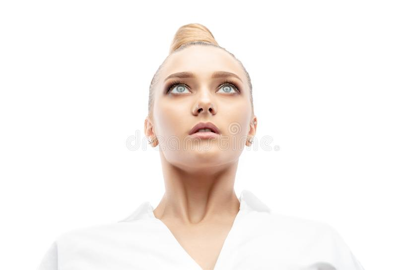 Beautiful spectacular blonde lady with an unusual high hairdo with big blue eyes on a white background stock images