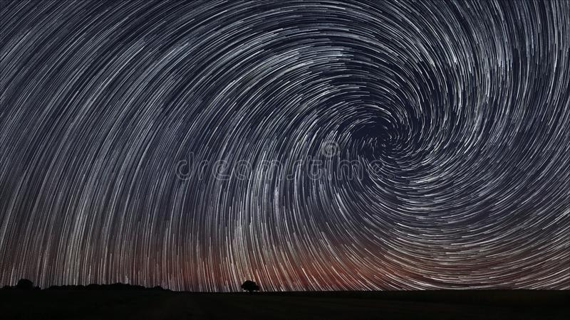 Beautiful Spiral Star Trails Over Filed With Lonely Tree