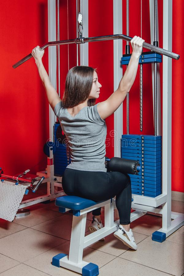 Beautiful sport girl is engaged on a simulator in the gym. Pretty girl with the beautiful tightened figure. Fitness girl stock photography