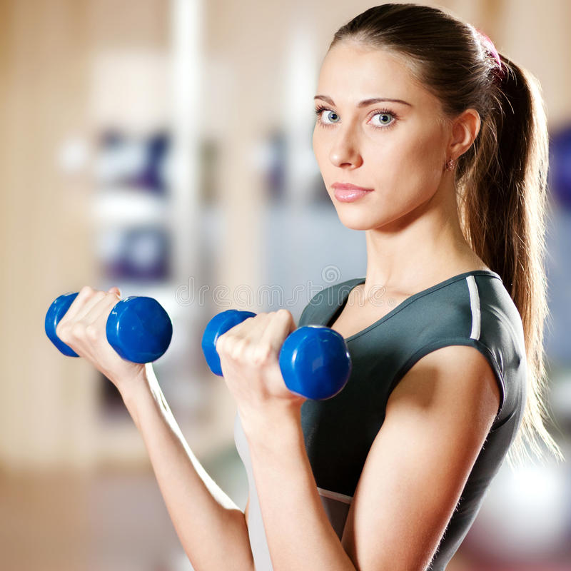 Beautiful sport woman doing exercise with dumbbell. Beautiful sport woman doing power fitness exercise at sport gym. Dumbbell stock photo