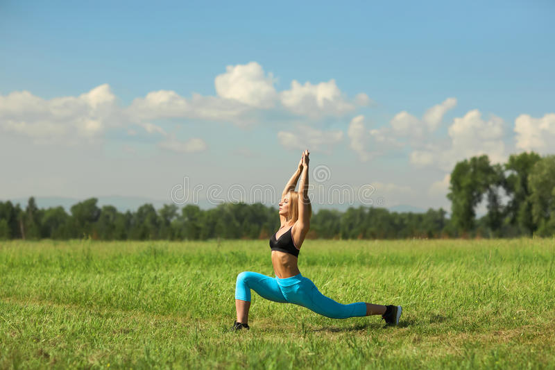 Beautiful sport woman doing stretching fitness exercise in city park at green grass. royalty free stock image