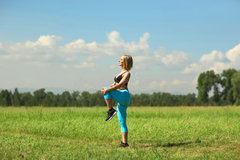 Beautiful sport woman doing stretching fitness exercise in city park at green grass. royalty free stock images