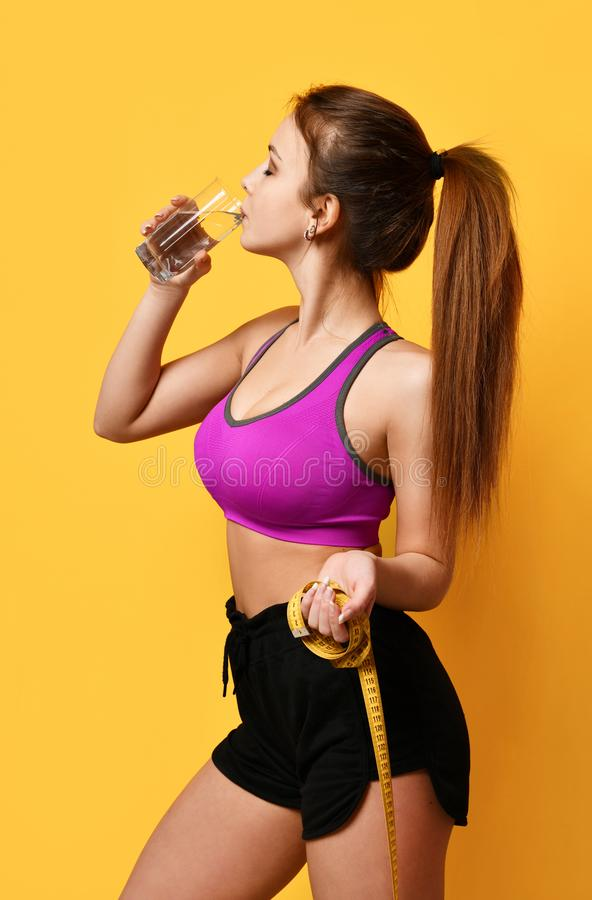 Beautiful sport woman hold tape measure and drinking water from glass on yellow background royalty free stock images