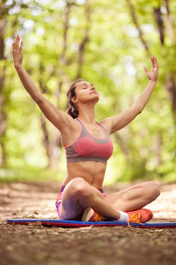 Young healthy beautiful woman is doing a yoga in the green park stock photo