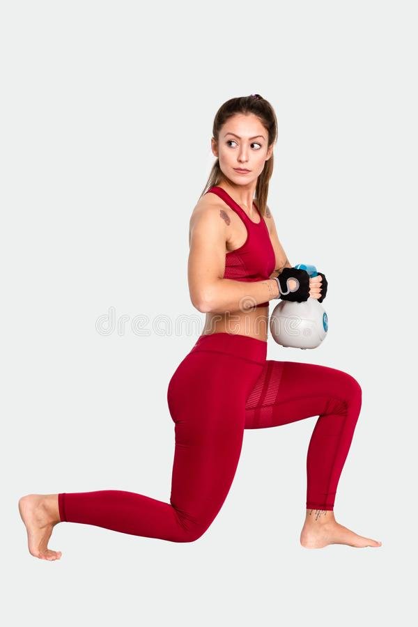 Beautiful sports girl is doing exercises with a kettlebell   - Image royalty free stock photo