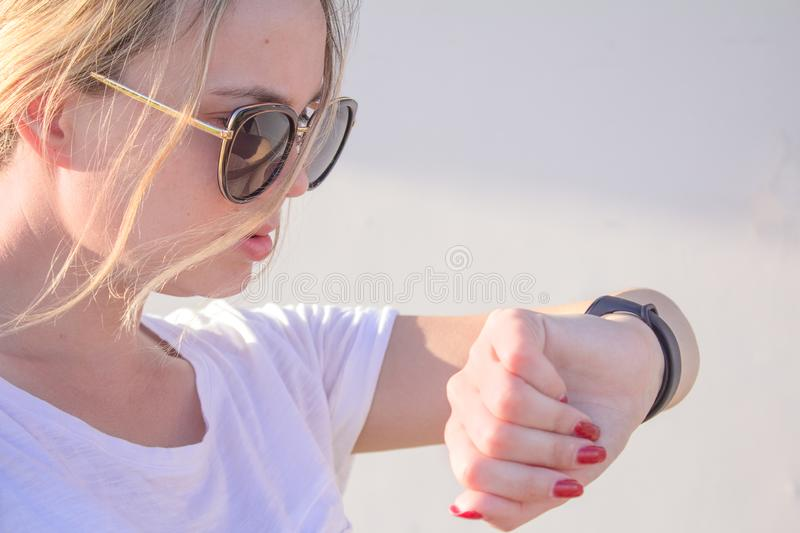 Beautiful sports girl is touching her fitbit bracelet after training. royalty free stock photos
