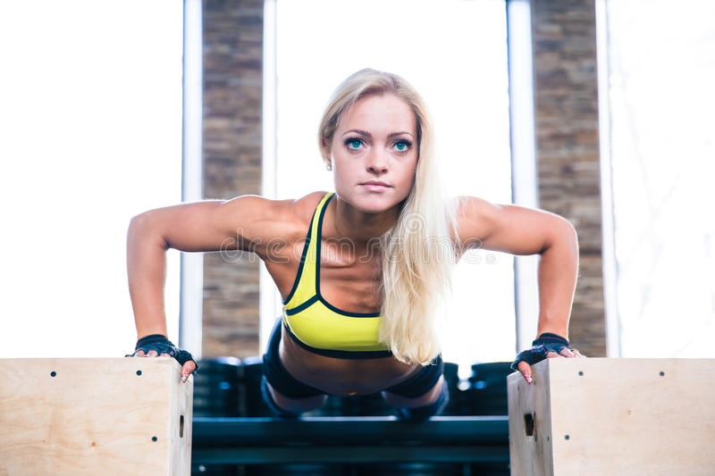 Beautiful sports woman doing push ups on fit box. Young beautiful sports woman doing push ups on fit box at gym stock photo