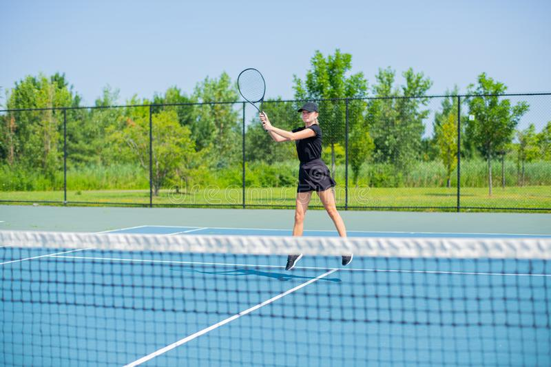 Young sports woman playing tennis on the blue tennis court stock photography