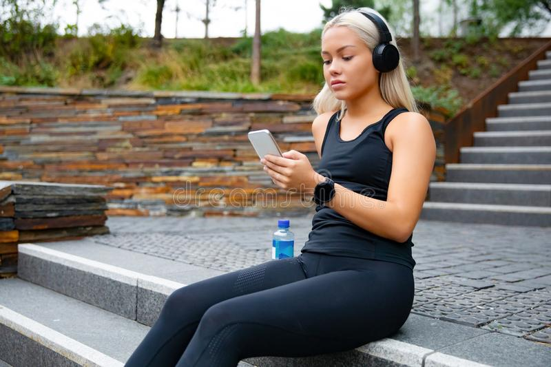 Beautiful sports woman sitting at stairs listen to music from smartphone royalty free stock image