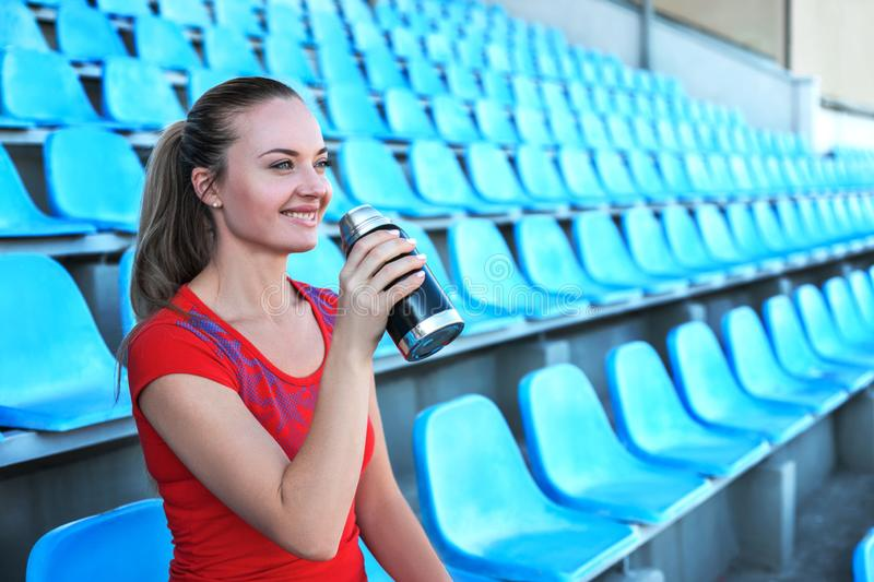 Beautiful sportswoman drinking water after work out. royalty free stock photography