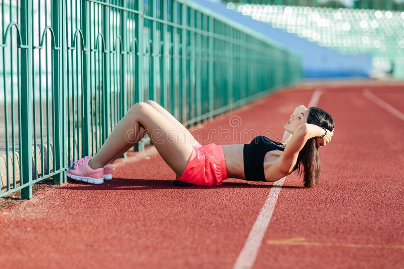 Beautiful sporty brunette woman in pink shorts and tank top appearance doing exercises on the stomach on the stadium track. Women. Beautiful sporty woman in pink stock images