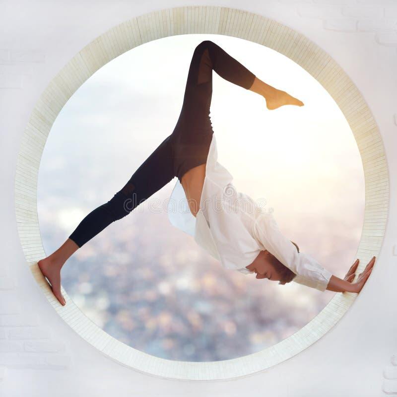 Beautiful sporty fit yogi woman practices yoga asana eka pada Adho Mukha Shvanasana - One Leg Downward Dog pose stock photography