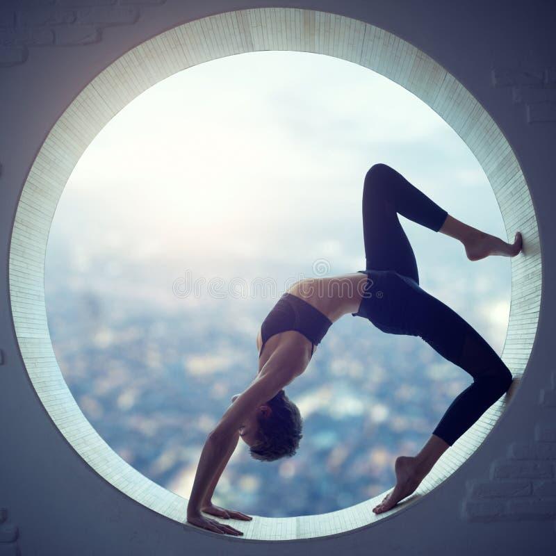 Beautiful sporty fit yogi woman practices yoga asana Eka Pada Urdhva Dhanurasana in a round window stock photo