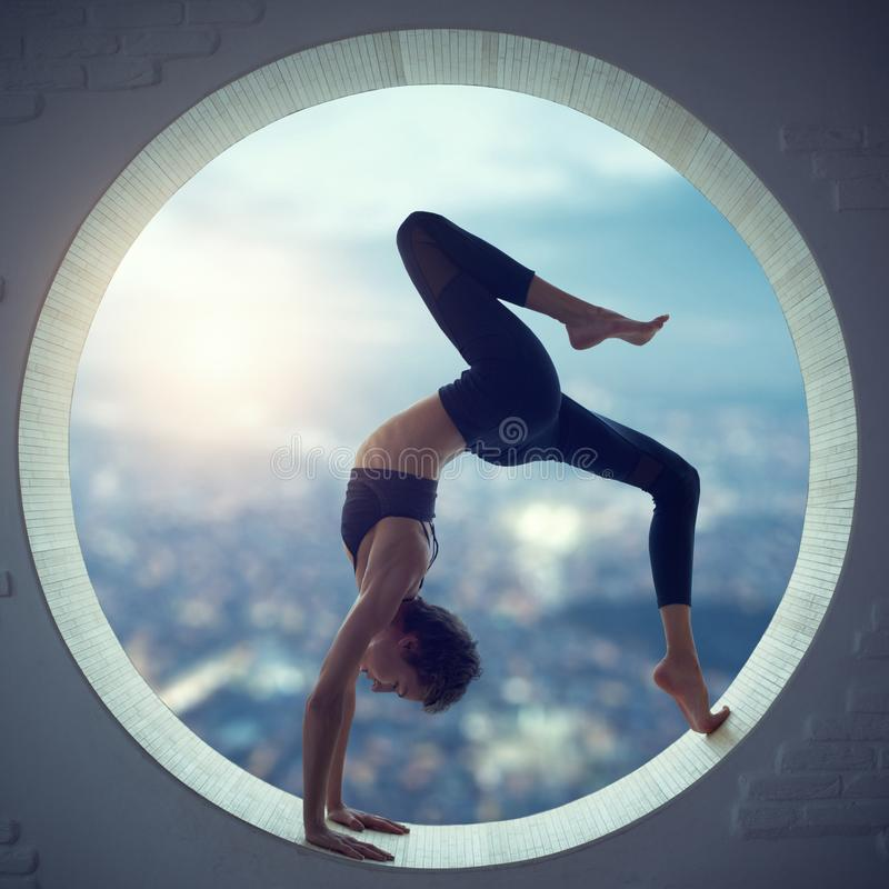 Beautiful sporty fit yogi woman practices yoga asana Eka Pada Urdhva Dhanurasana in a round window stock photo