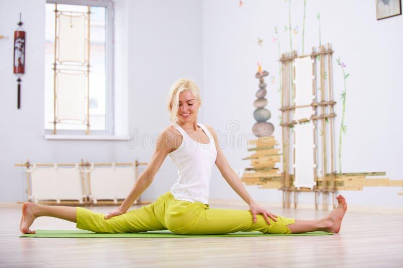 Beautiful sporty fit yogi woman practices yoga asana Hanumanasana - Monkey pose in the fitness room royalty free stock images