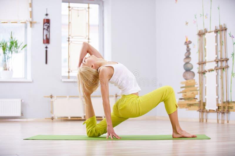 Beautiful sporty fit yogi woman practices yoga asana King Pigeon pose rajakapotasana in the fitness room royalty free stock image
