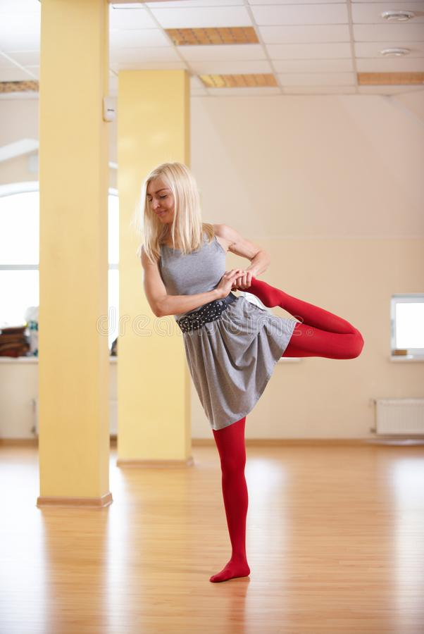 Beautiful sporty fit yogi woman practices yoga asana Natarajasana - Lord Of The Dance pose in the fitness room royalty free stock photography