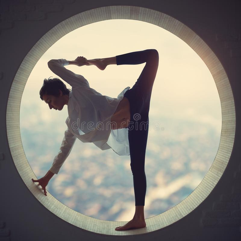 Beautiful sporty fit yogi woman practices yoga asana Natarajasana - Lord Of The Dance pose in a round window at sunset stock photo