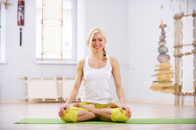 Beautiful sporty fit yogi woman practices yoga asana Padmasana - Lotus pose in the fitness room royalty free stock photo