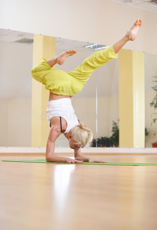 Beautiful sporty fit yogi woman practices yoga asana Vrischikasana Scorpion pose in the fitness room royalty free stock photos
